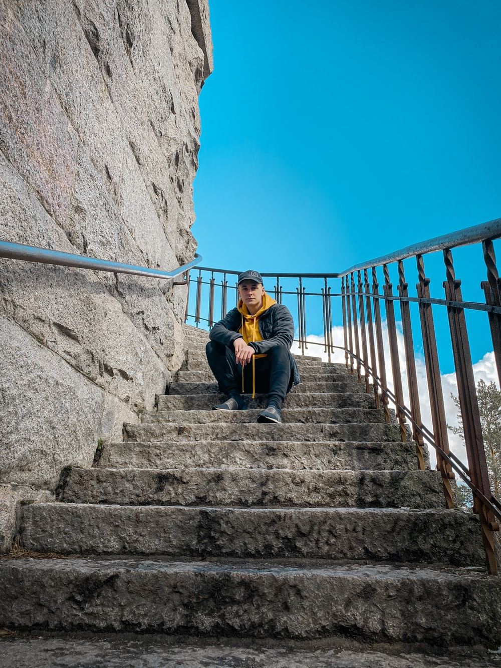 woman in black jacket sitting on stairs