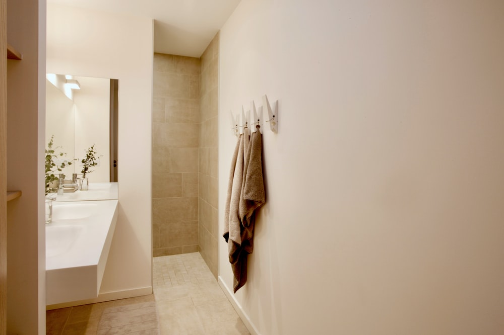 white bath towel hanging on white wall