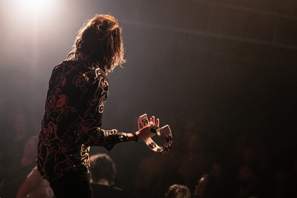 woman in black and red floral long sleeve shirt playing guitar on stage