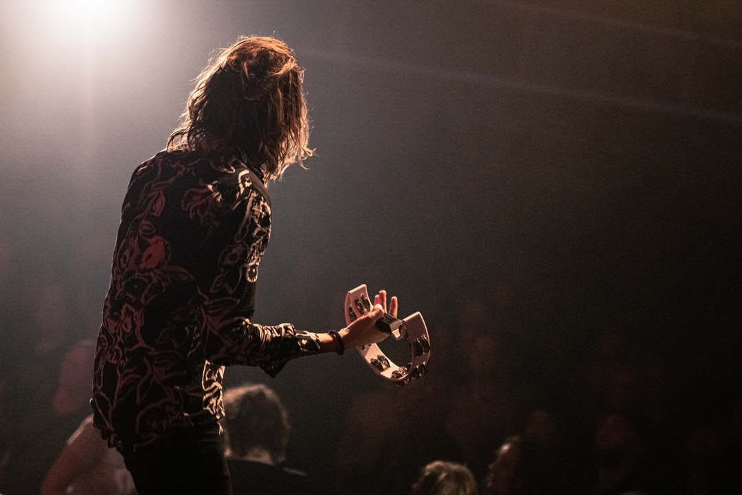 A musician in backlight standing in front of the audience and playing tambourine