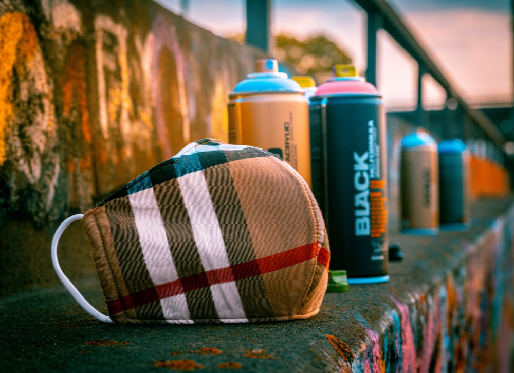 blue and white plaid pouch beside blue and white plastic bottle