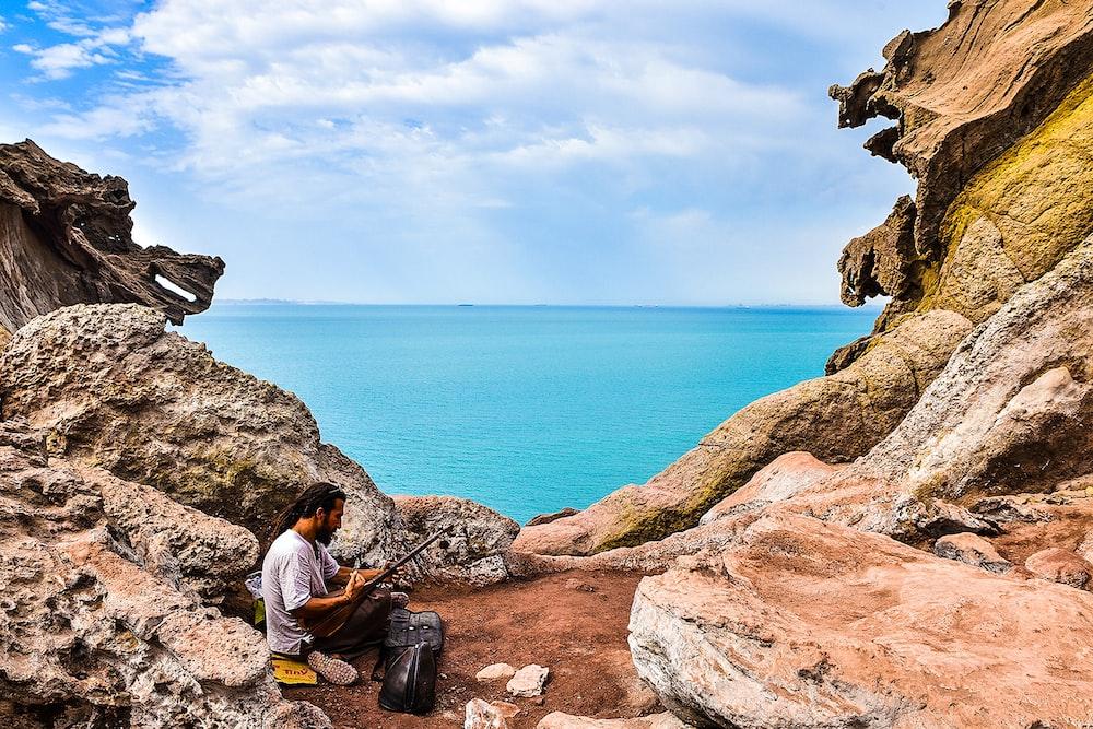 man in orange jacket sitting on brown rock formation near body of water during daytime