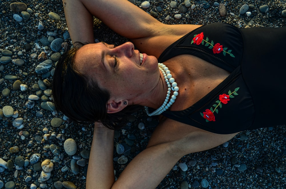 woman in black and red tank top lying on gray rocks