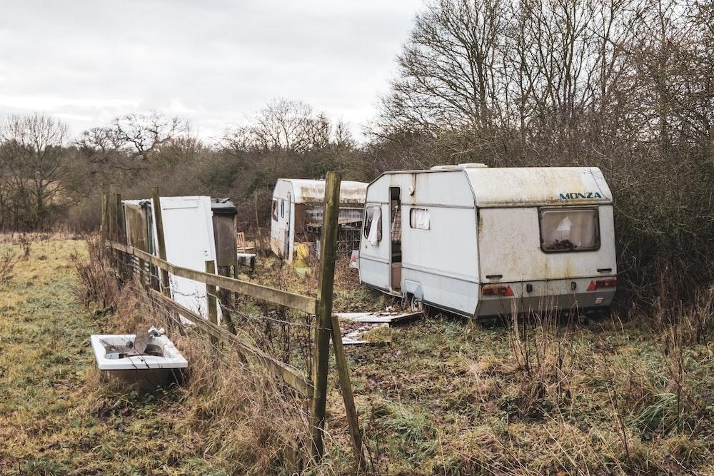 white rv trailer on green grass field during daytime