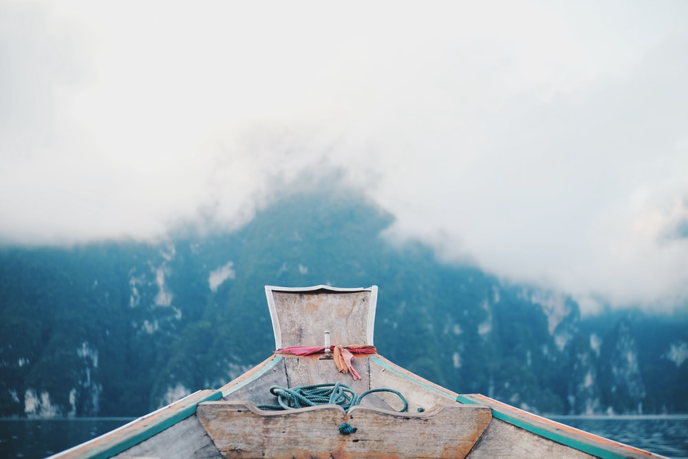 white and green boat on body of water during daytime