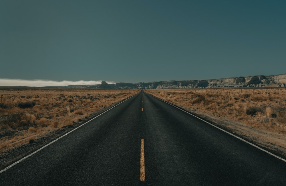 black asphalt road between brown grass field under blue sky during daytime