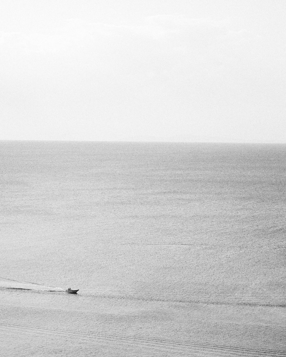 grayscale photo of person in boat on sea