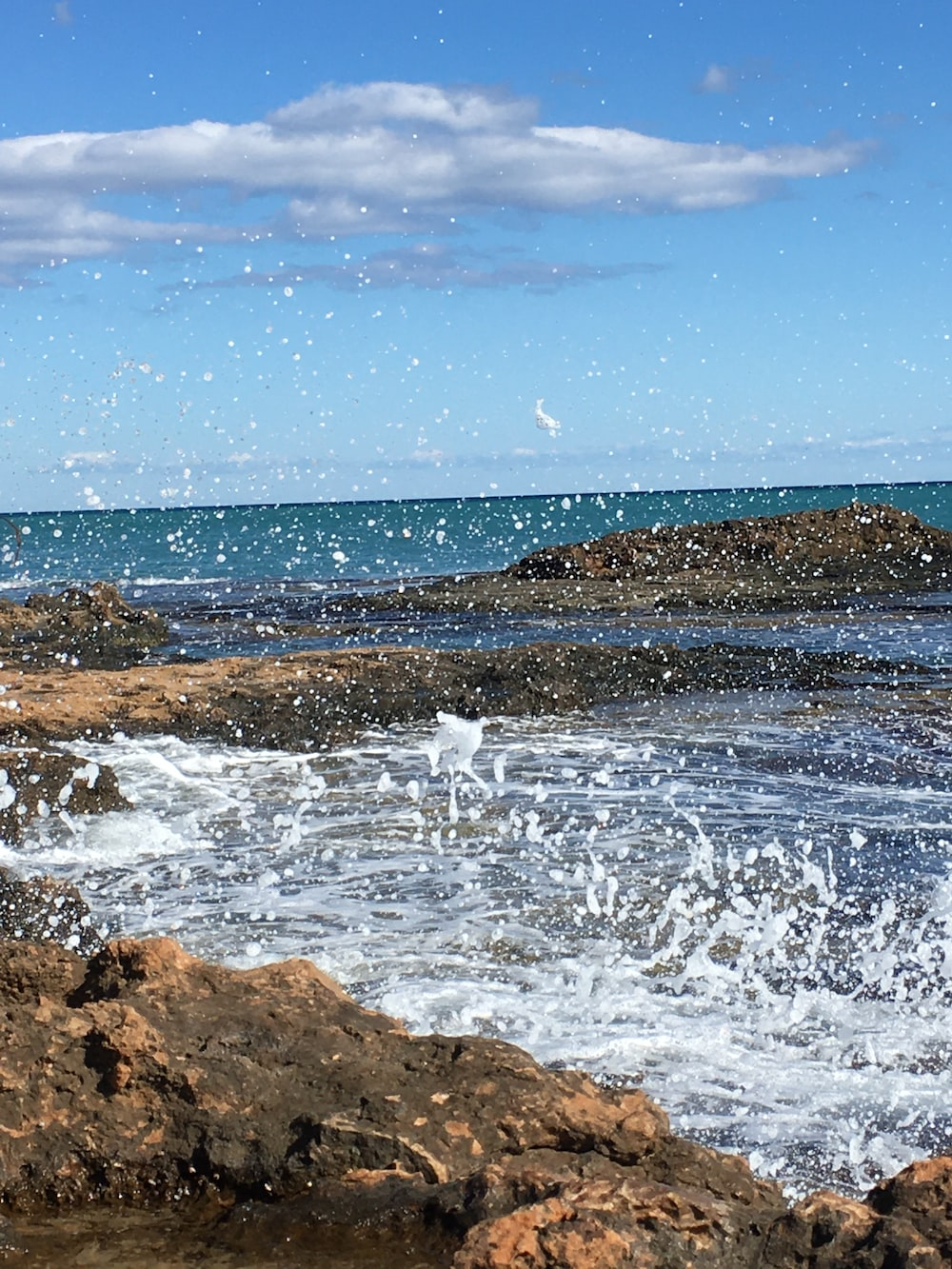 ocean waves crashing on brown rocky shore under blue and white cloudy sky during daytime