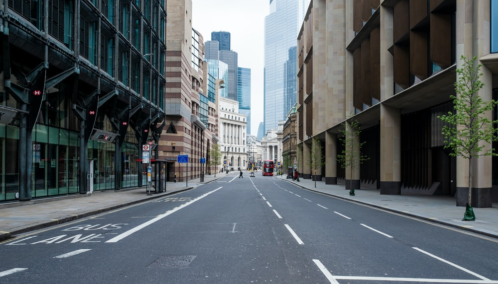 gray concrete road between high rise buildings during daytime