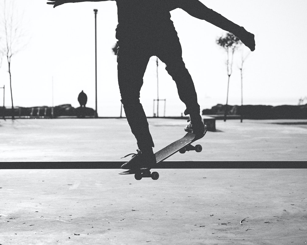 man in black pants and black shoes playing skateboard