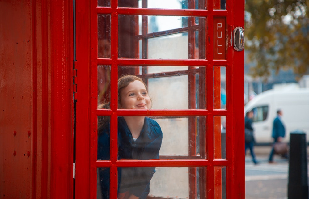 woman in black long sleeve shirt leaning on red telephone booth