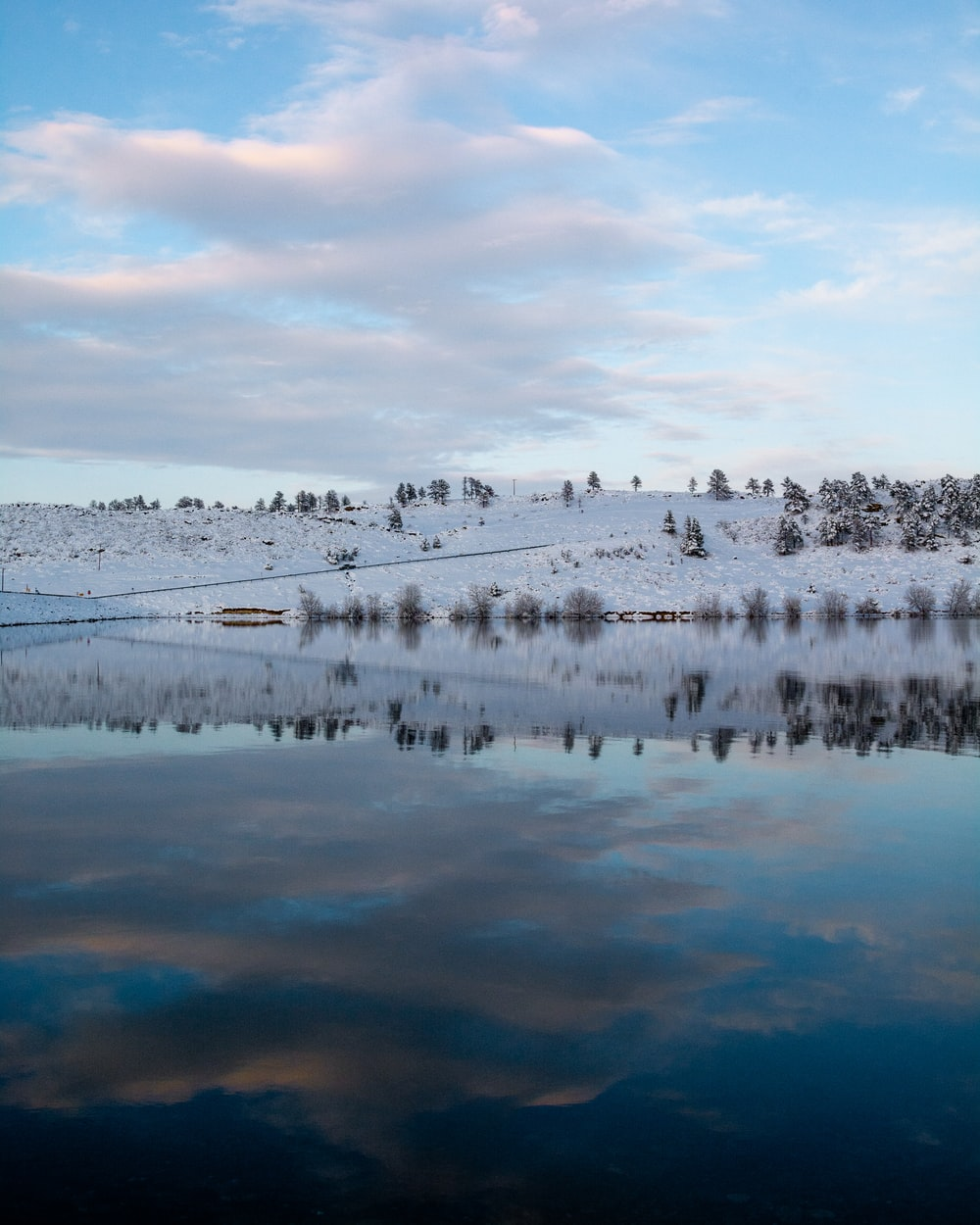 body of water with snow covered ground under cloudy sky during daytime