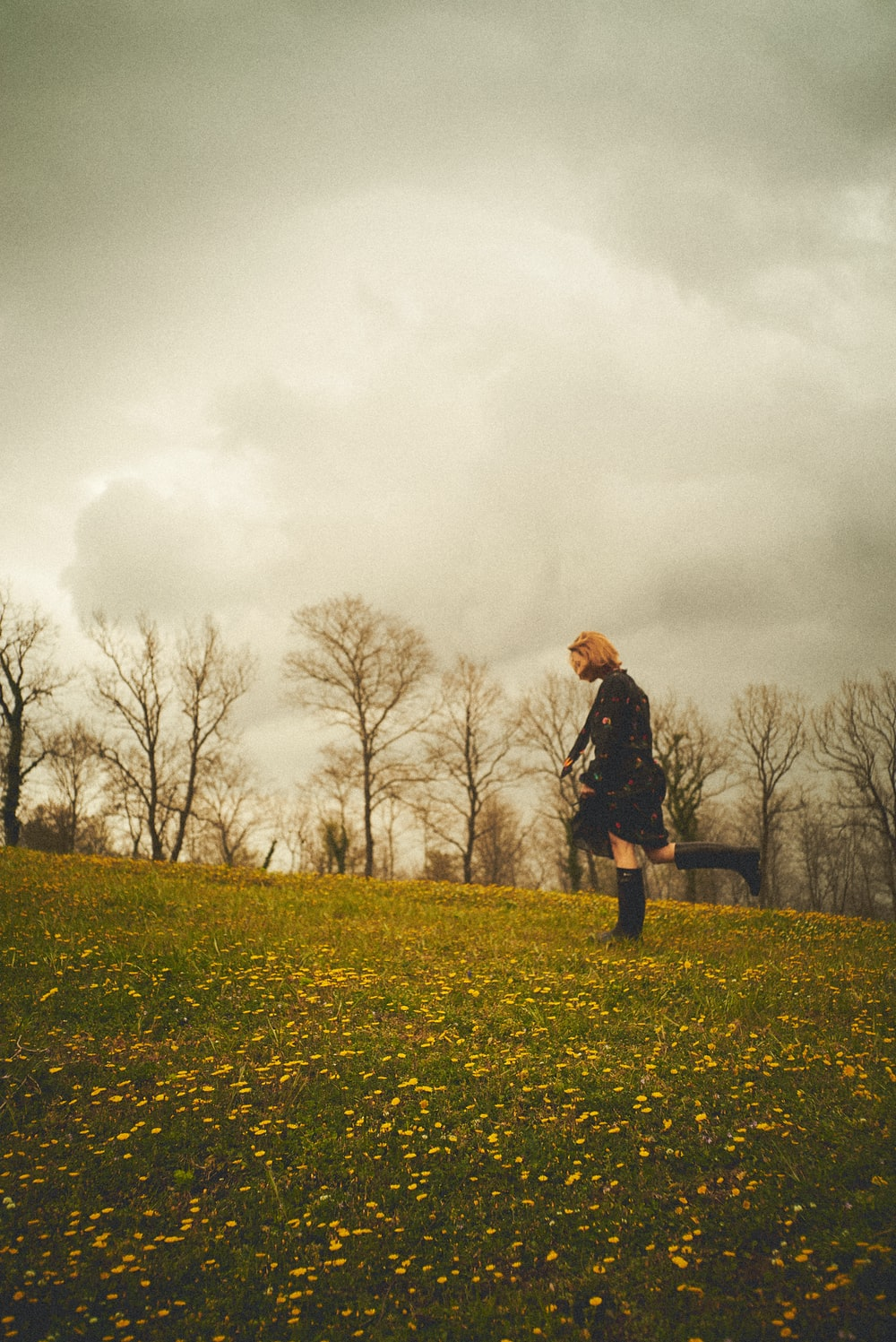 man in black jacket standing on green grass field under gray cloudy sky
