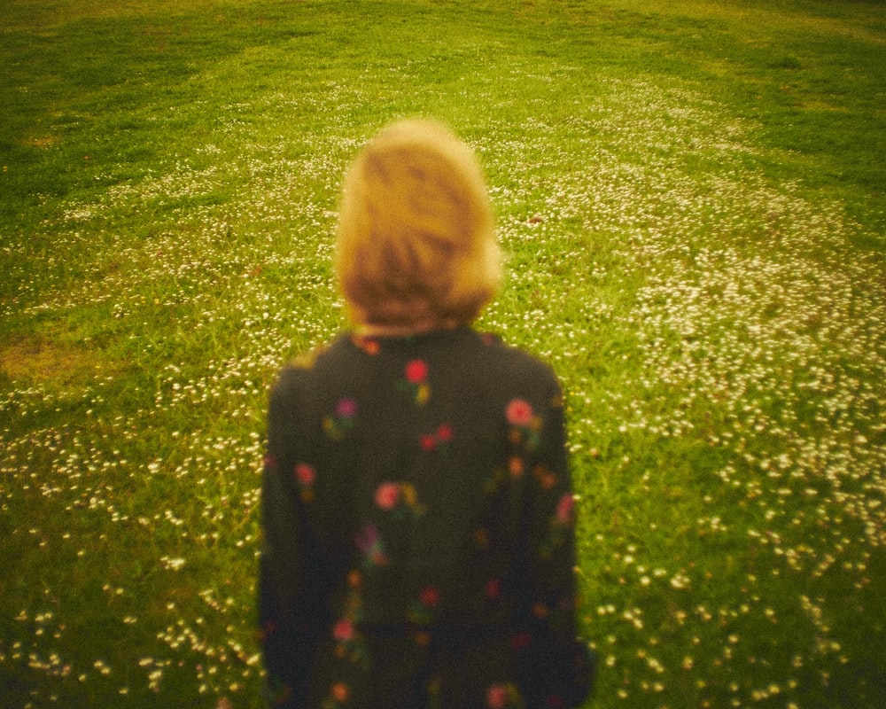 girl in black and green polka dot long sleeve shirt standing on green grass field during