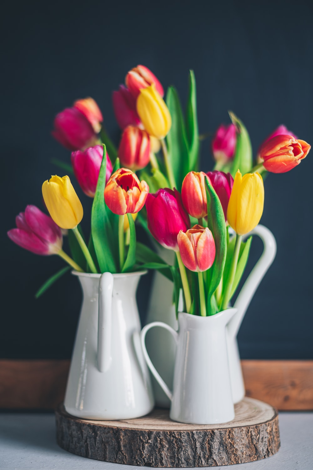 red and yellow tulips in white ceramic vase