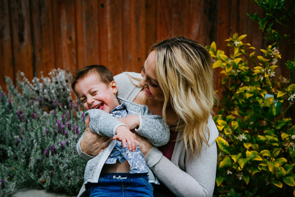 woman in gray sweater carrying baby in blue and white shirt