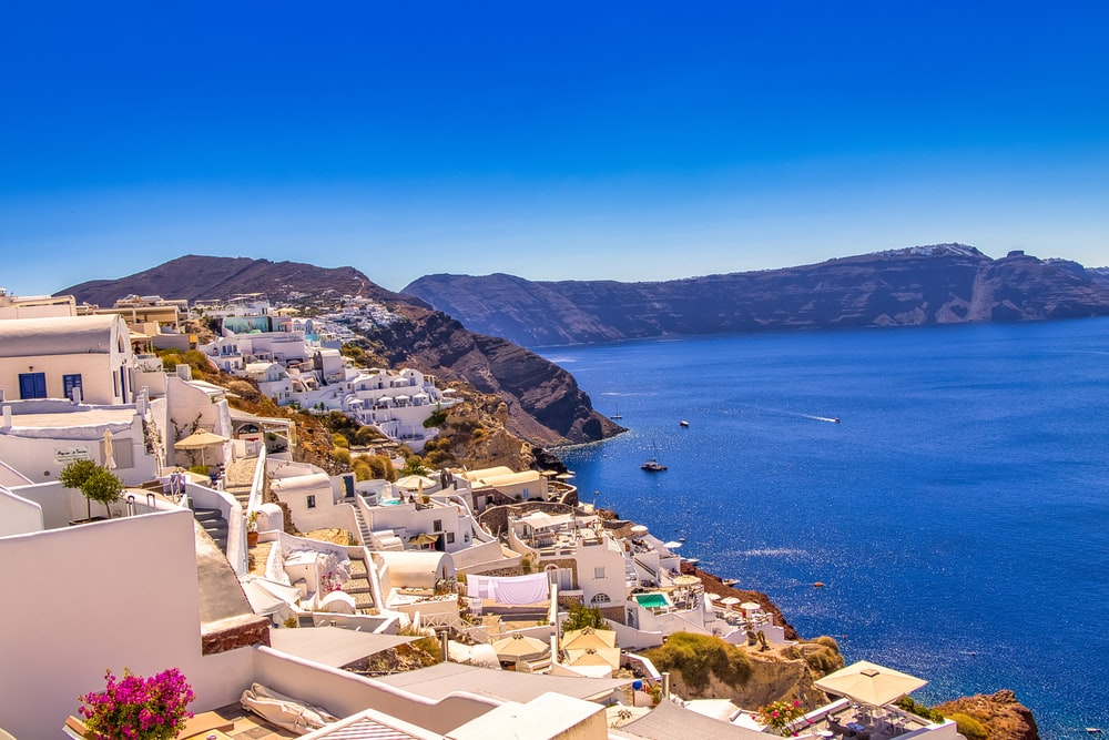 white and brown houses near blue sea under blue sky during daytime