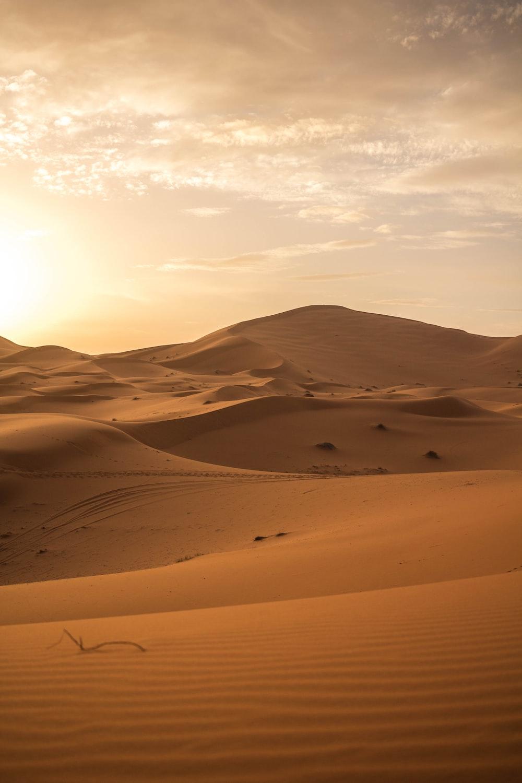 brown sand under white clouds during daytime