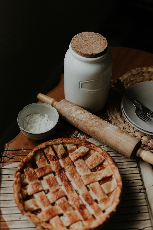 white ceramic mug beside brown wooden rolling pin