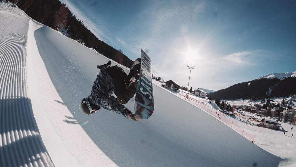 man in black jacket and black pants riding snowboard during daytime