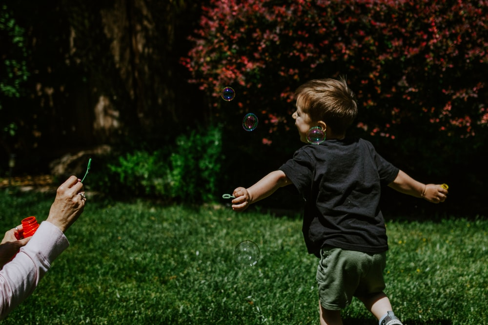 boy in black t-shirt and green shorts playing bubbles on green grass field during daytime