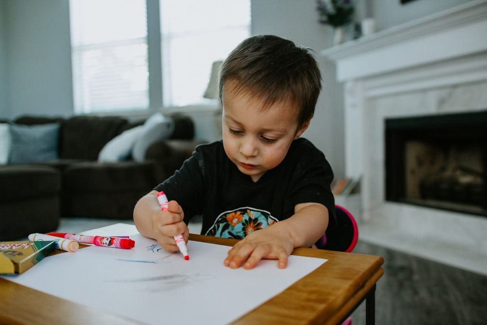 boy in black crew neck shirt writing on white paper