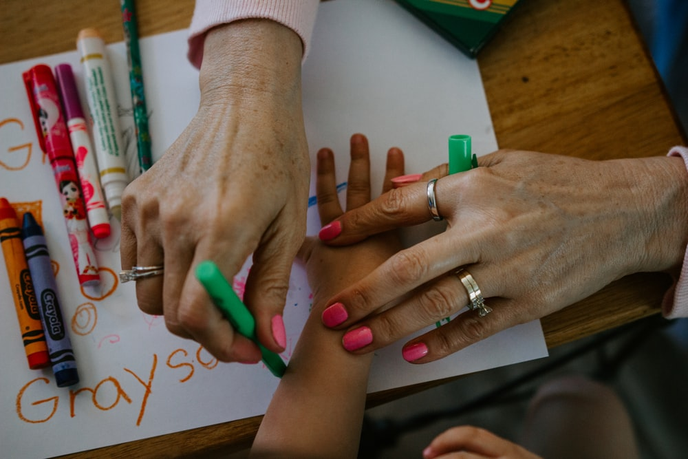 person wearing silver ring and green manicure