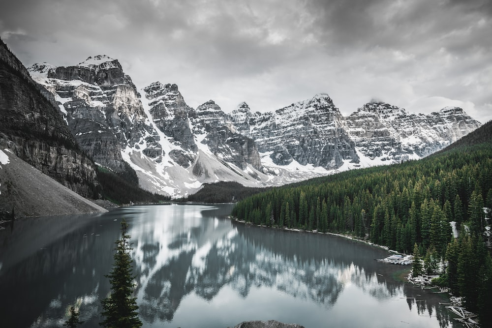 lake near snow covered mountain under cloudy sky during daytime