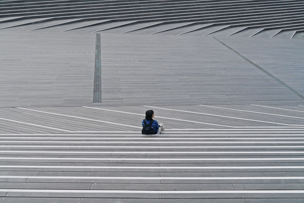 person in black jacket sitting on white and gray concrete floor