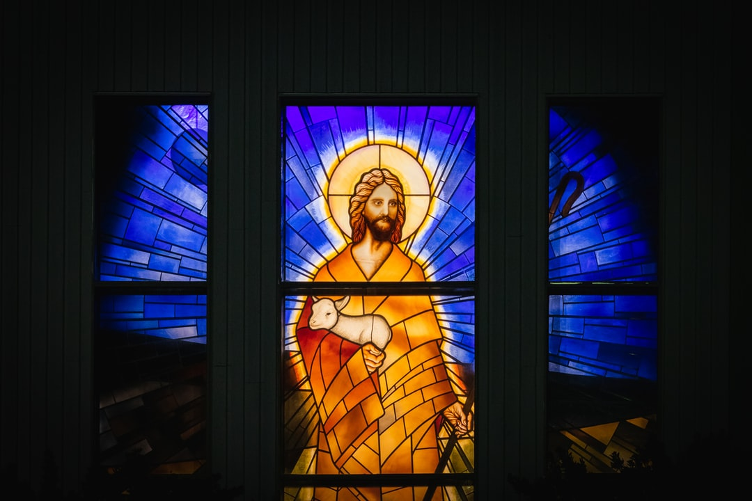 colourful stained glass window of Jesus Christ carrying a lamb