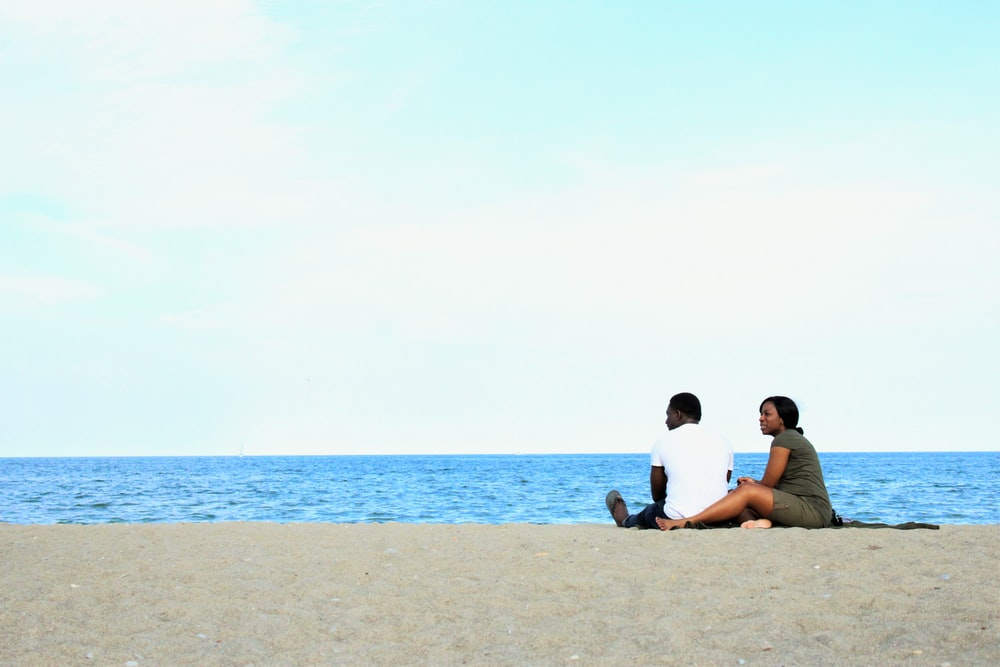 couple sitting on beach during daytime