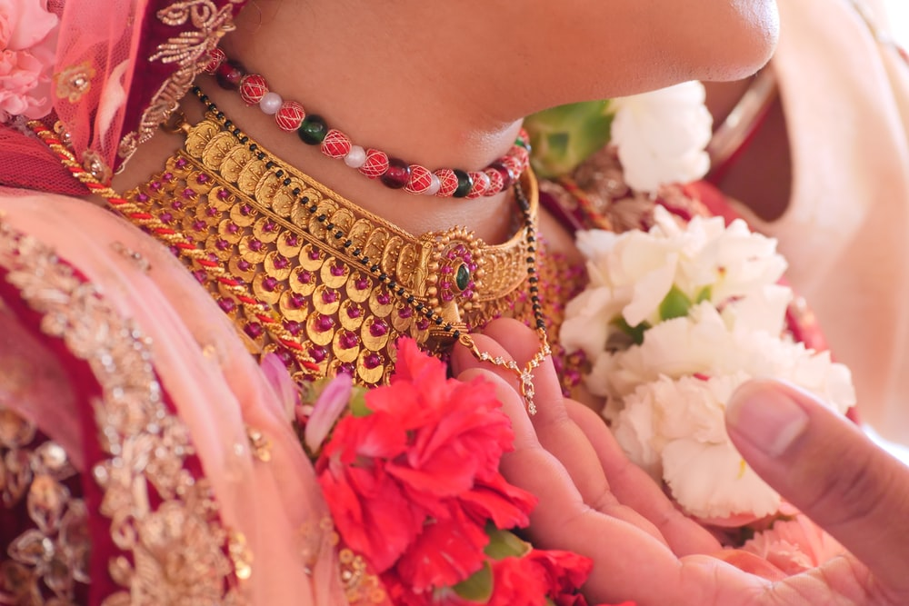 woman wearing gold and pink beaded bracelet