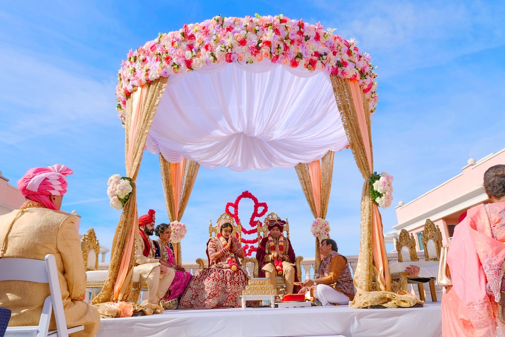people sitting on chair under red and white floral umbrella