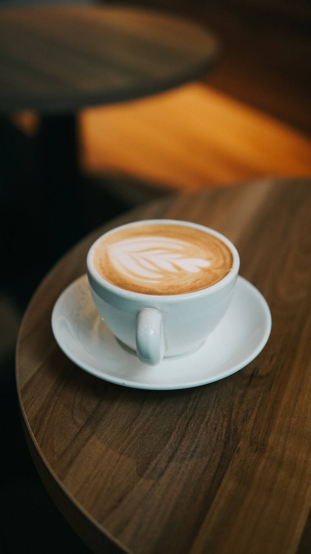 white ceramic cup with cappuccino on white ceramic saucer