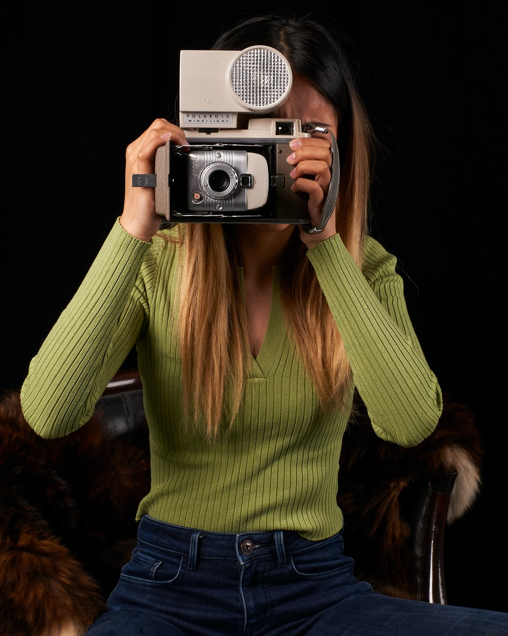 woman in green sweater holding silver and black camera