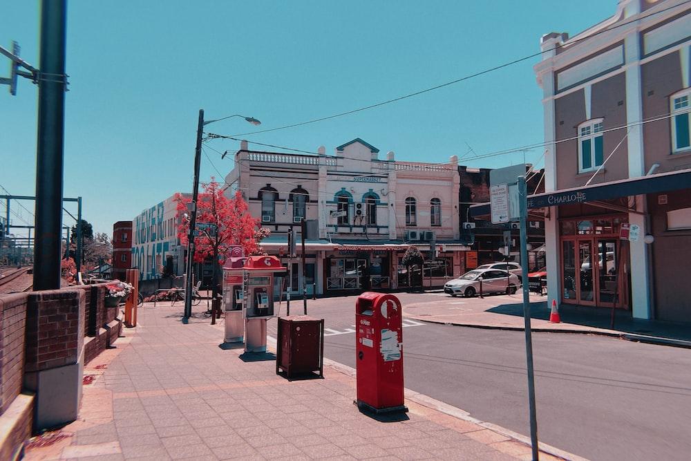 red trash bins on sidewalk during daytime