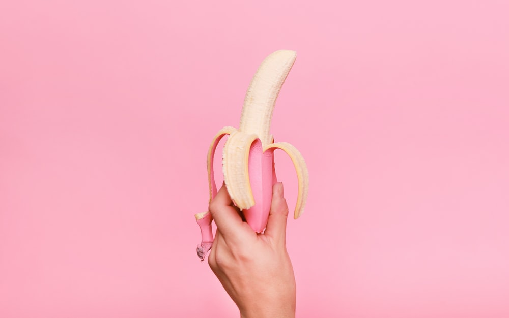 person holding sliced of banana
