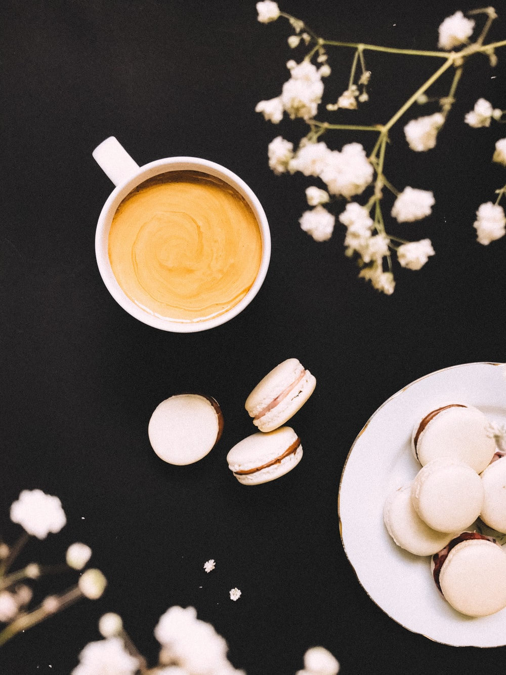 white ceramic mug with coffee on white ceramic saucer