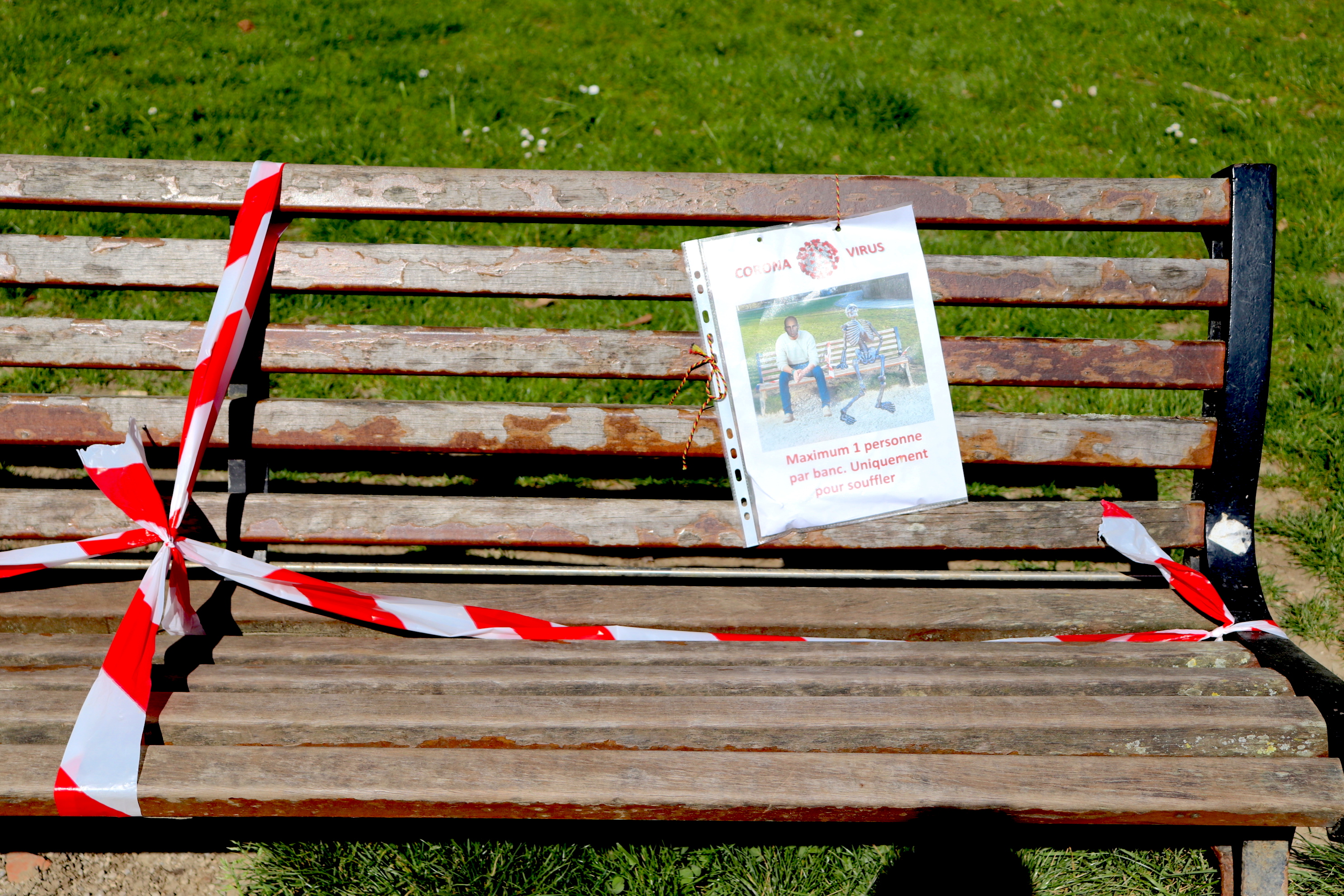park bench with poster telling visitors to keep physical distance or become a sceleton