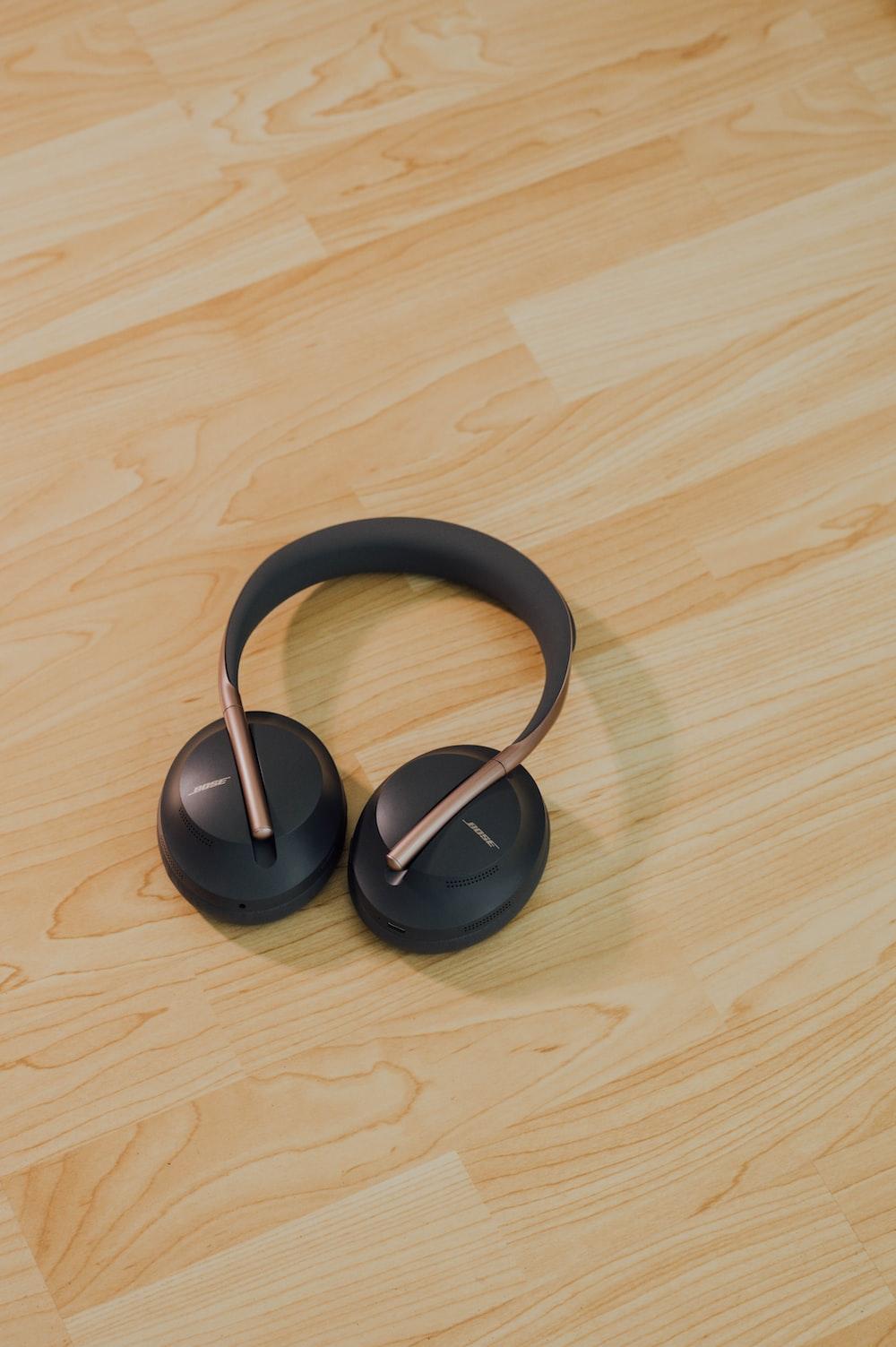 black wireless headphones on brown wooden floor