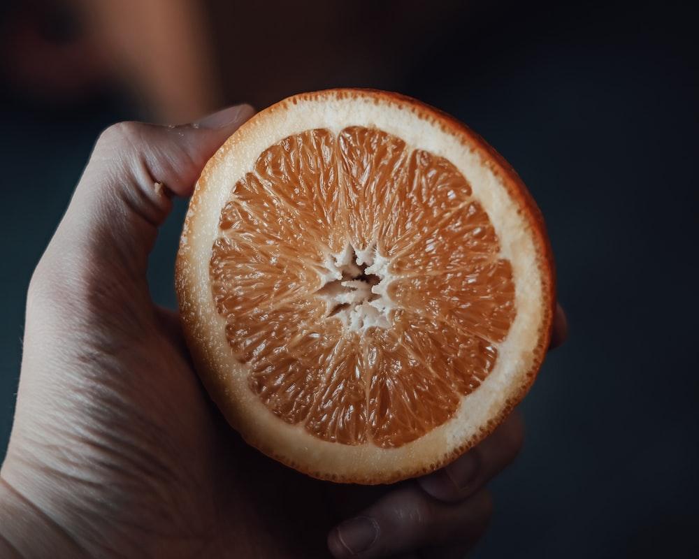 person holding orange citrus fruit