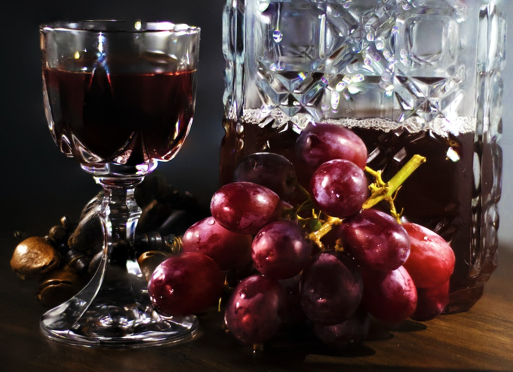 red round fruit beside clear wine glass