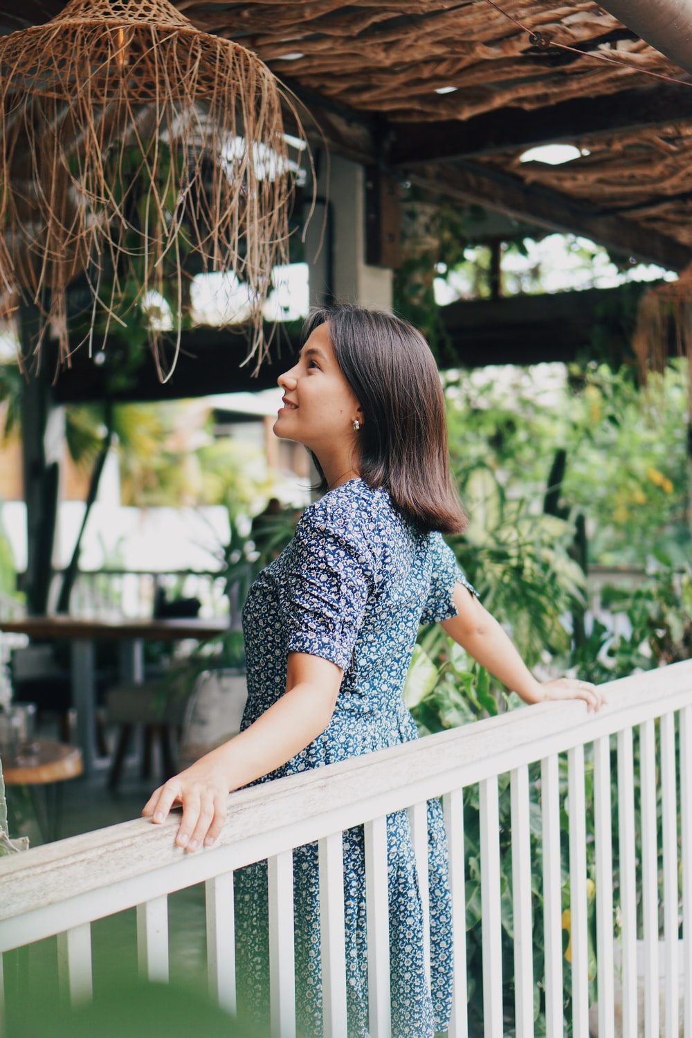 woman in blue and white floral shirt sitting on brown wooden bench during daytime