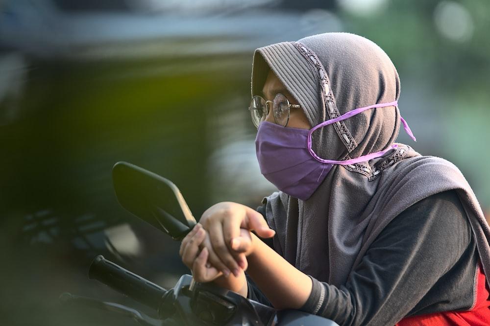 woman in black hoodie wearing purple hijab