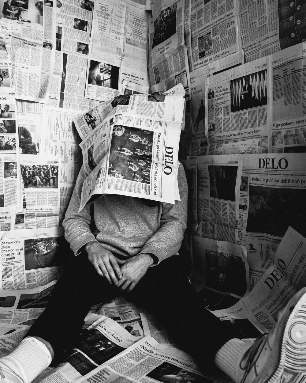 grayscale photo of person in long sleeve shirt holding newspaper