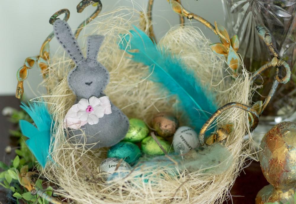 gray rabbit plush toy on brown nest