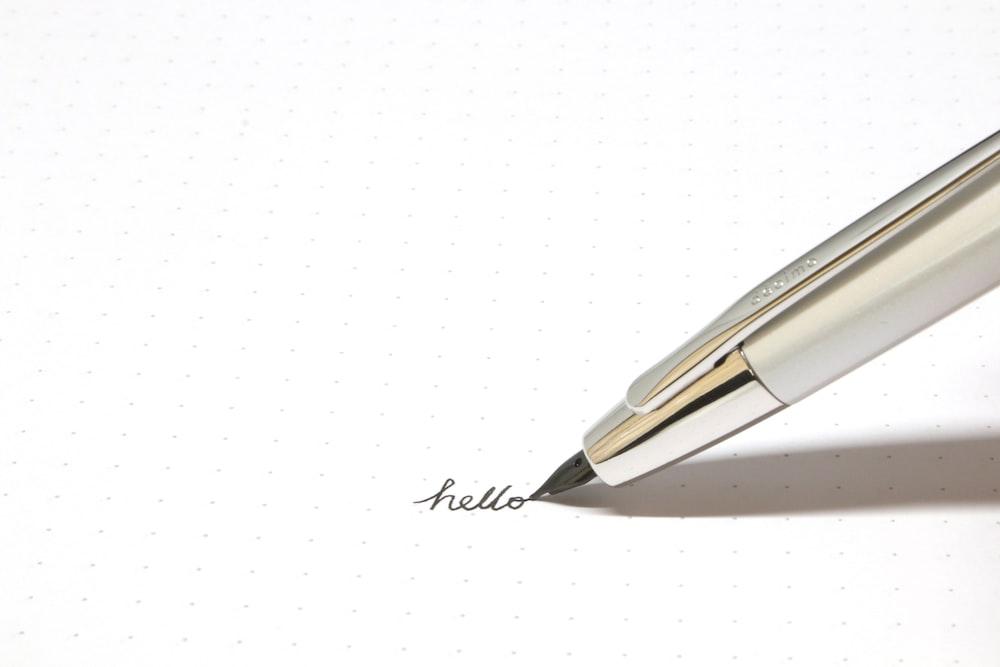 silver click pen on white paper