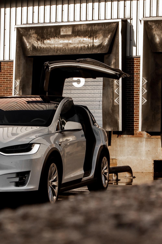 silver sedan parked beside brown brick wall