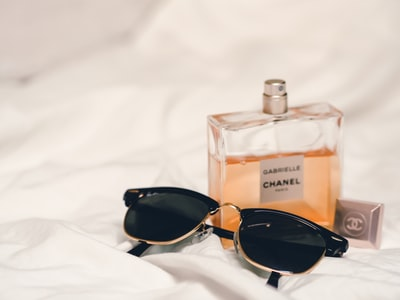 black sunglasses beside perfume bottle