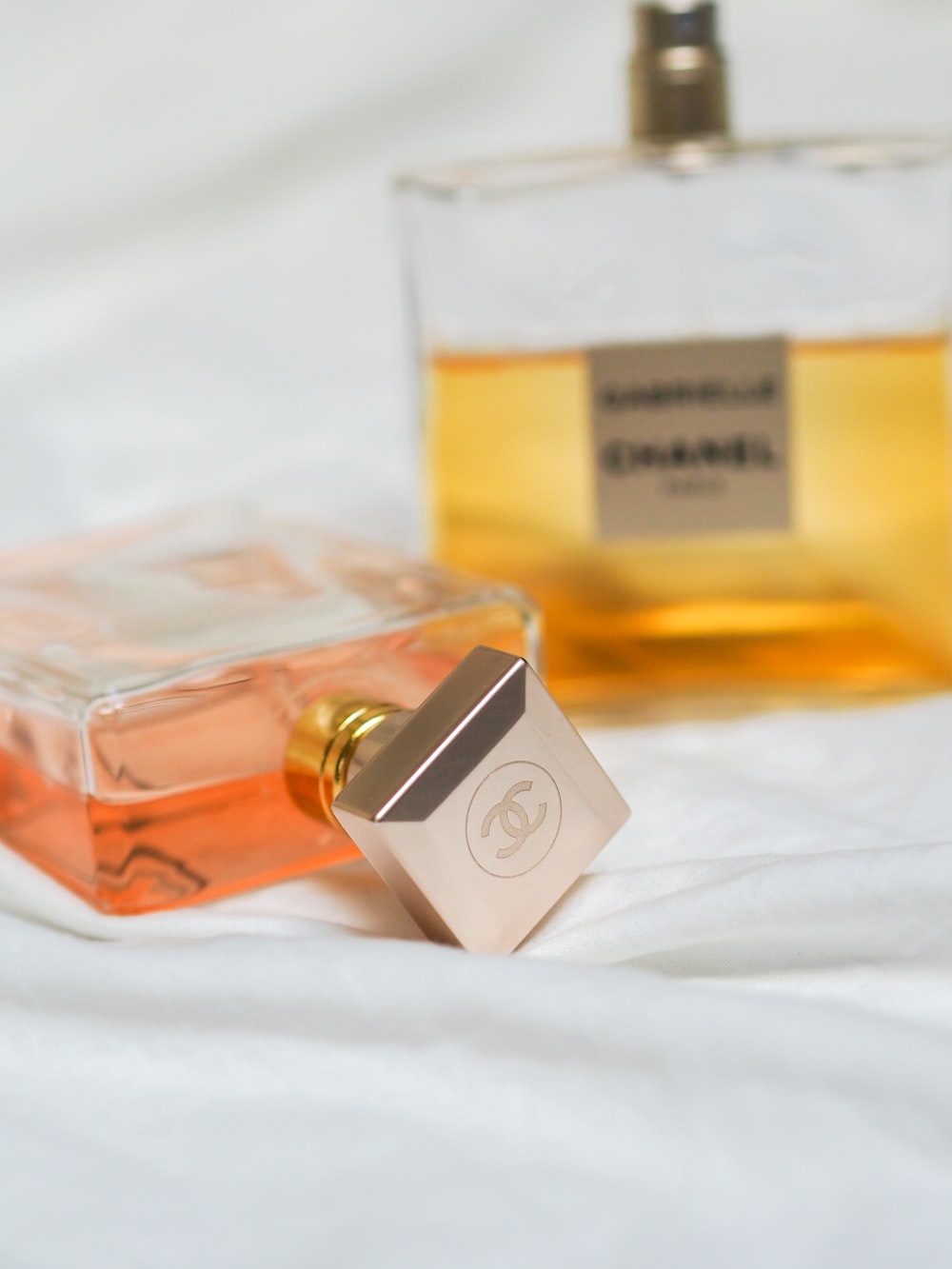 gold and silver perfume bottle on white textile